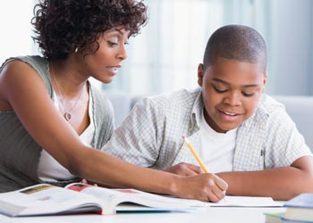 Mother working with her son on homework. Getty Images Royalty Free